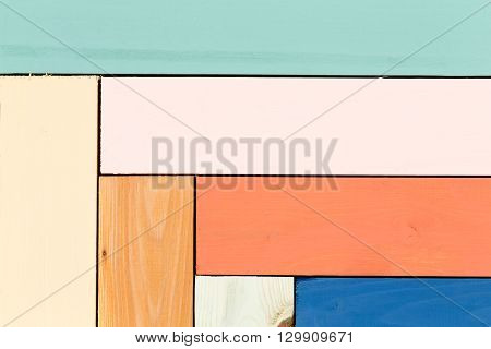 Close up view on background with copy space of green pink yellow orange blue and stained wood boards