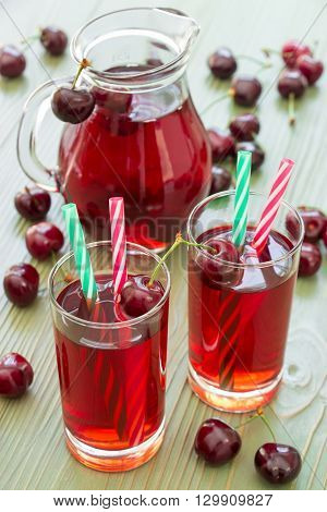 Two glasses of cherry juice with straws in the foreground and in the background a jar full of cherry juice. 2 cherry juices. Vertical. Close-up. Daylight.