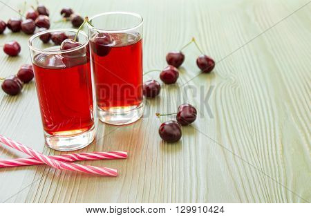 Left two glasses of cherry juice around scattered cherries, right empty space for text on light green background.  2 cherry juices, straws and empty space. Horizontal. Close. Daylight.