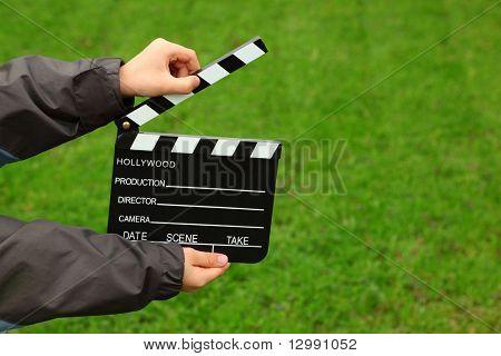 Kino Clapper Board in Händen des jungen Jacke auf Feld mit grünem Gras