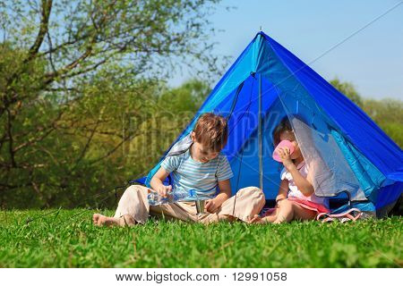 brother and sister drinking water in tent outdoor