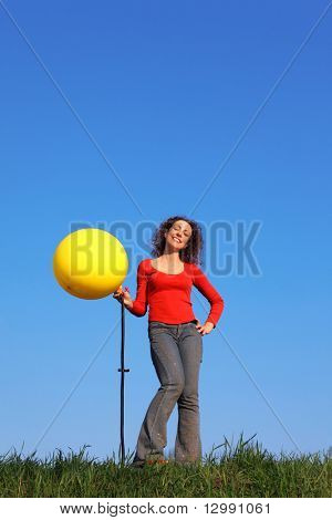 Girl stands in meadow with green grass against blue sky and inflates with foot pump yellow balloon