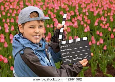 Boy in jacket and cap with cinema clapper board in their hands standing on field with tulips