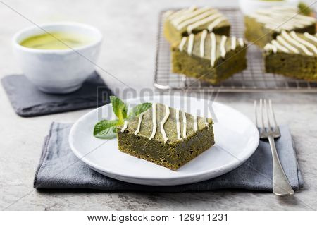 Matcha green tea brownie cake with white chocolate on a white plate. Grey stone background