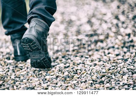 Person walking forward with boots on stones