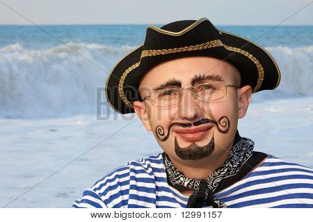 portrait of smiling man with drawed beard and whiskers in pirate suit. sea wave in out of focus.