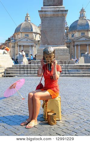 young woman in mask of Egyptian pharaoh and pink umbrella at Piazza del Popolo in Rome, Italy