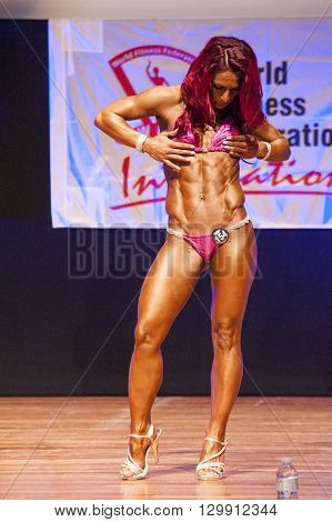 MAASTRICHT THE NETHERLANDS - OCTOBER 25 2015: Female fitness model flexes her muscles and shows her best physique in a abdominal and thighspose on stage at the World Grandprix Bodybuilding and Fitness of the WBBF-WFF