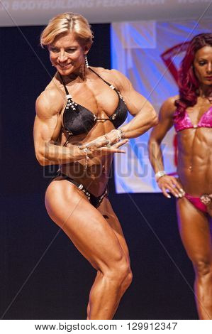 MAASTRICHT THE NETHERLANDS - OCTOBER 25 2015: Female fitness model Gerbel Mikk flexes her muscles and shows her best physique in a chest pose on stage at the World Grandprix Bodybuilding and Fitness of the WBBF-WFF
