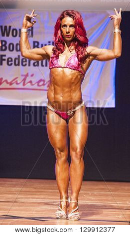 MAASTRICHT THE NETHERLANDS - OCTOBER 25 2015: Female fitness model flexes her muscles and shows her best physique in a front double biceps pose on stage at the World Grandprix Bodybuilding and Fitness of the WBBF-WFF