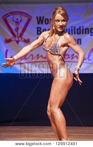 MAASTRICHT THE NETHERLANDS - OCTOBER 25 2015: Female fitness model flexes her muscles and shows her best physique in a sidepose on stage at the World Grandprix Bodybuilding and Fitness of the WBBF-WFF on October 25 2015 at the MECC Theatre