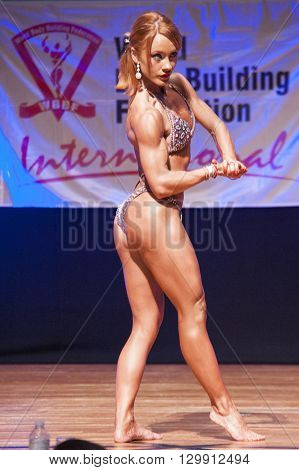 MAASTRICHT THE NETHERLANDS - OCTOBER 25 2015: Female fitness model flexes her muscles and shows her best physique in a chest pose on stage at the World Grandprix Bodybuilding and Fitness of the WBBF-WFF on October 25 2015 at the MECC Theatre