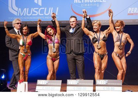 MAASTRICHT THE NETHERLANDS - OCTOBER 25 2015: Female bodybuilders Gerbel Mikk Sonja den Breems- Tanamal and others celebrate their victory with the officials on stage at the World Grandprix Bodybuilding and Fitness of the WBBF-WFF