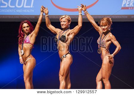MAASTRICHT THE NETHERLANDS - OCTOBER 25 2015: Female bodybuilders Gerbel Mikk and others celebrate their victory on stage at the World Grandprix Bodybuilding and Fitness of the WBBF-WFF on October 25 2015 at the MECC Theatre in Maastricht