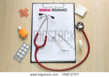 Top view of medical insurance policy with stethoscope hypodermic syringe plaster gauze tincture and tape.