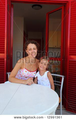 Mother with daughter sit on  verandah  round table and hold on to  hands