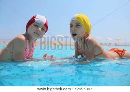 Two girls lie in  day-time in  pool opposite each other and speak