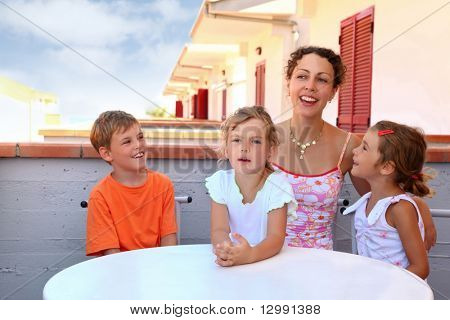 Two girls with boy and mother sit in  day-time on  balcony near  table and speak merrily, focus on little girl in center