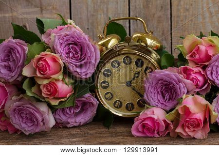 bouquet of fresh pink and violet  fresh roses with golden vintage clock