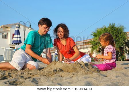 Mother with father and girl sit in  day-time on  beach and build hills from sand