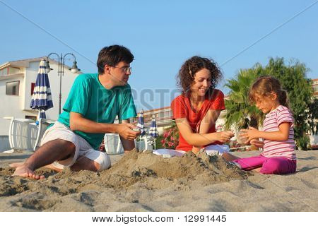 Father with  mother and daughter sit on  beach in  day-time and play on sand