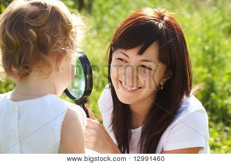 Mother and daughter looking at each other through a magnifying glass