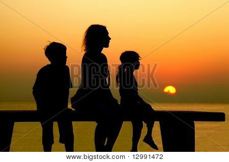 Mother with two children sits on  bench and looks at  beach toward sunset