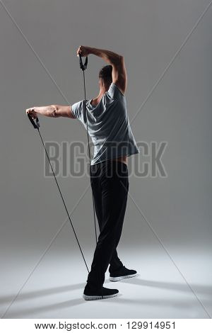 Back view portrait of a fitness man workout with expander over gray background