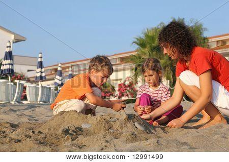 Mutter mit zwei Kindern befindet sich am Strand in tagsüber und Build-Hügel aus sand
