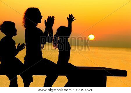 Mother with two children sits on  bench on  beach on sunset and merrily slam hands