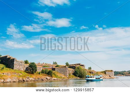Tourist Boat Floats Near The Sea Fortress Of Suomenlinna. Historic Suomenlinna, Sveaborg Maritime Fortress In Helsinki, Finland. Sunny Day With Blue Sky