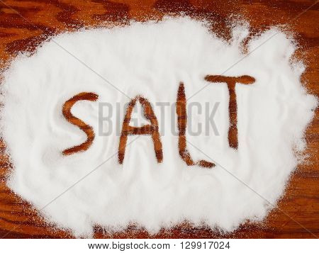Salt spilled on wooden table with word SALT