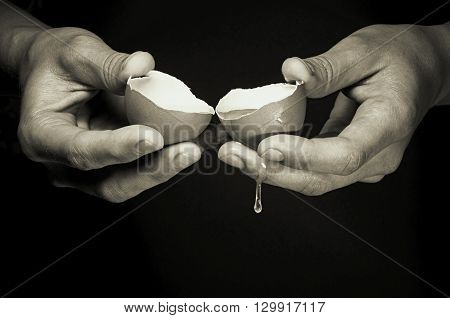 female hands breaking a raw egg on black background b/w