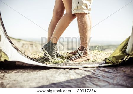 Couple kissing out their tent. Couple on a camping excursion on the hills