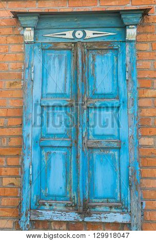 Old window with closed wooden shutters in an old Ukrainian country house