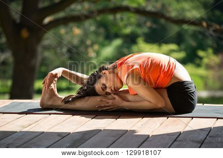 Brunetter girl is engaged in yoga on the wooden terrace on the nature background. She seated forward bend on the black yoga mat. Her head lies on the left knee, left hand is on left leg, right hand is on the feet. Her eyes are closed. She wears black shor