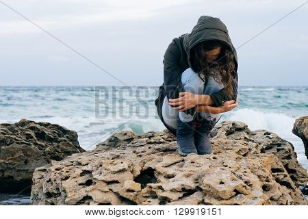 Girl in the green jacket with hood sits alone on a rocky on a cold cloudy day