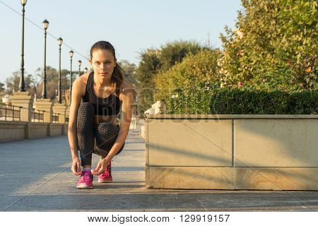 Slim girl in a sports pants and a bra tying laces on pink sneakers and preparing for a jog in the park early morning