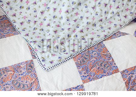 Patchwork quilt. Part of patchwork quilt as background. Flower print. Print cucumbers. A violet blanket in style patchwork. Color blanket. Handmade.