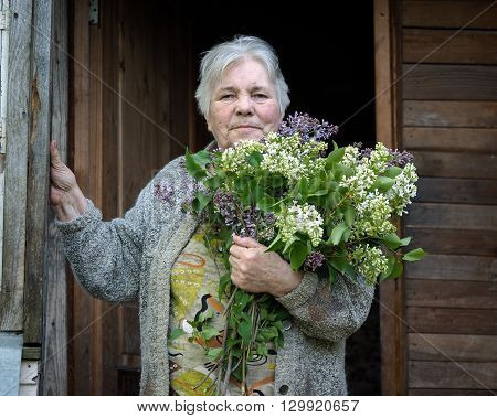 Portrait of an elderly woman with a big bouquet of lilac. An old house. Grandma smiles. The woman has gray hair, a lot of wrinkles