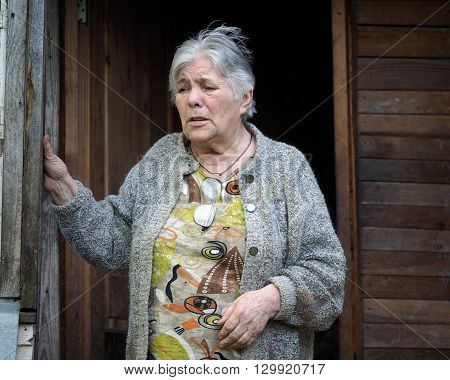 Portrait of an elderly woman. Old house doorway. Grandma sad. The woman has gray hair, a lot of wrinkles.