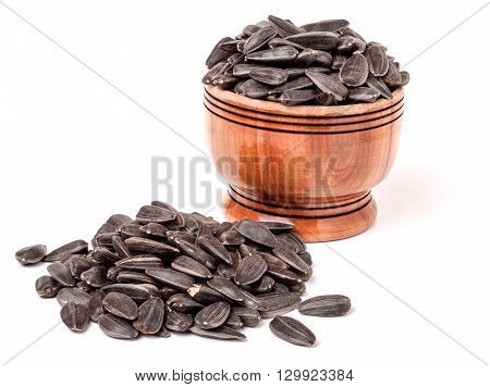 unpeeled sunflower seeds spill out of wooden barrels on a white background