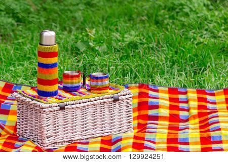 Picnic on the grass. Picnic basket with thermos of tea.