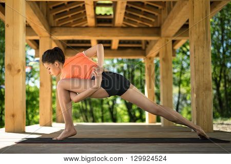 Yoga girl makes low lunge with left leg forward on the black yoga mat on the wooden terrace on the nature background. She holds her hands together on her back and left hand is clasping left leg. Her eyes are closed. She wears orange t-shirt and black shor