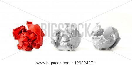 Red paper ball next to two white ones as a symbol of difference and variety of society and ideas.