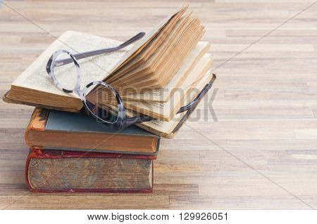 Books stack with open one and glasses, copy space  on wooden table desktop