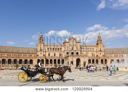 Seville, Spain - April 30, 2016: A sunny day at Plaza de Espana, tourists visiting the famous square, a horse-drawn carriage passing by in foreground