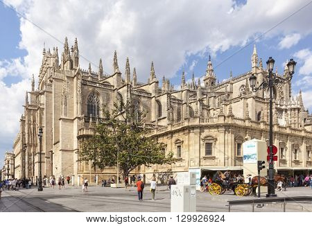 Seville Cathedral, view from the south, horse-drawn carriage in front, people walking by. Santa Maria de la Sede is the largest gothic cathedral worldwide and belongs to UNESCO world heritage.