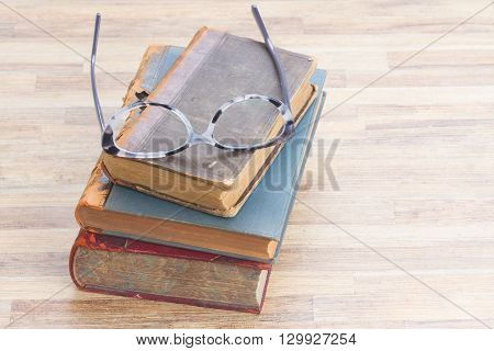 Books stack and glasses on wooden table background