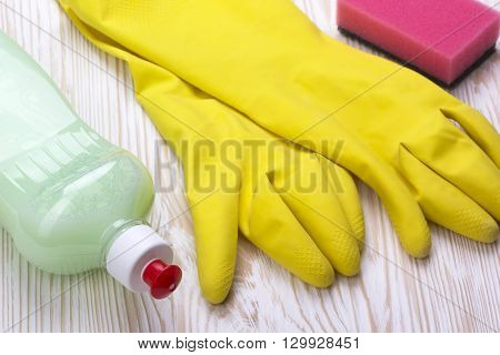 Detergent, sponge  and latex gloves on wooden background
